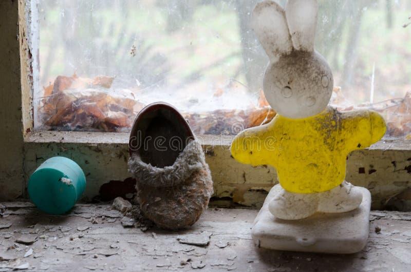 Barns leksak och skor på fönsterbräda i övergett dagis i förstörd by av zonen för Kopachi Tjernobyl NPP-avlägsnande arkivfoton