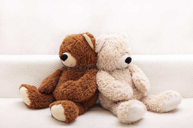 Barns leksaker - bj?rnar av brun och beige f?rg sitter p? soffan royaltyfri fotografi