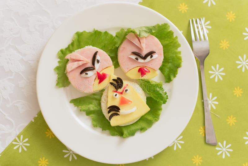 Barns mat, roliga fågel-formade smörgåsar Barns meny på en grön bakgrund arkivbilder