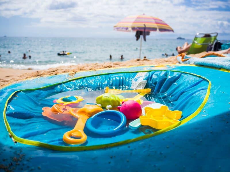 Barns pöl med leksaker på sanden royaltyfri bild