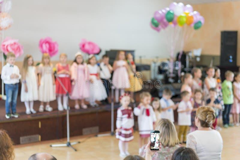 Barns parti i grundskola för barn mellan 5 och 11 år Unga barn på etapp i dagis syns främsta föräldrar oskarpa tillbaka skola til royaltyfri fotografi
