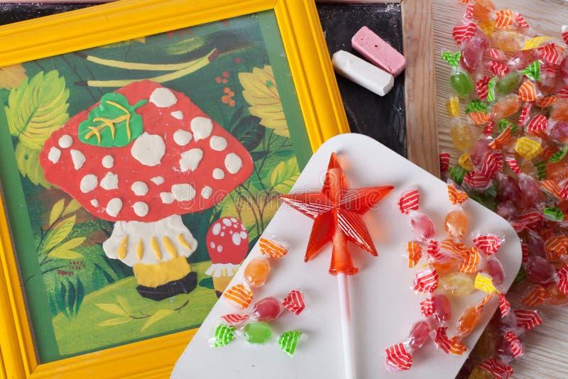 Barns stilleben för höst för amanita för champinjon för teckningsplasticine på en klubba för godis för färgpennor för tabellbräde arkivfoto