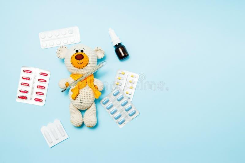 Barns tar den stack björnen för leksaknallen med piller temperaturen av en kvicksilverexponeringsglastermometer på blå bakgrund fotografering för bildbyråer