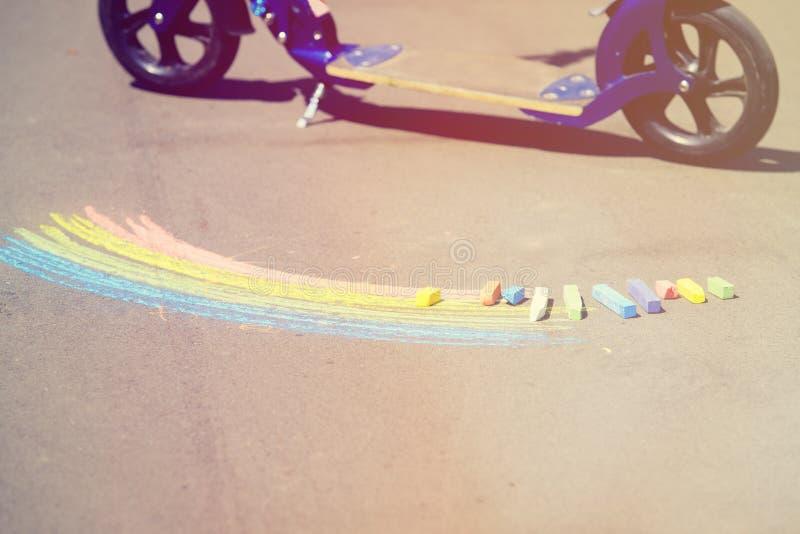 Barns teckning av regnbågen och färgrika chalks på fotografering för bildbyråer