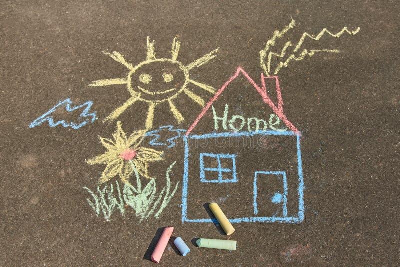 Barns teckning med krita på asfalten: ett hus med den inskrifthemmet, solen och blomman royaltyfri foto