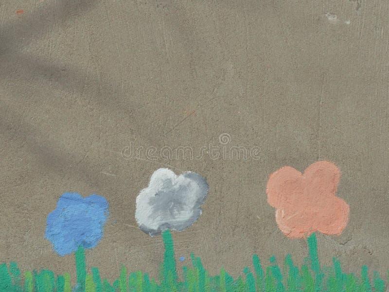 Barns teckning på den gråa väggen av husblommorna arkivfoto