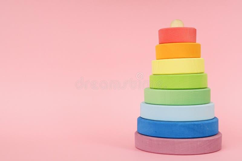 Barns trämång--färgade pyramid på en rosa bakgrund med copyspace royaltyfria foton