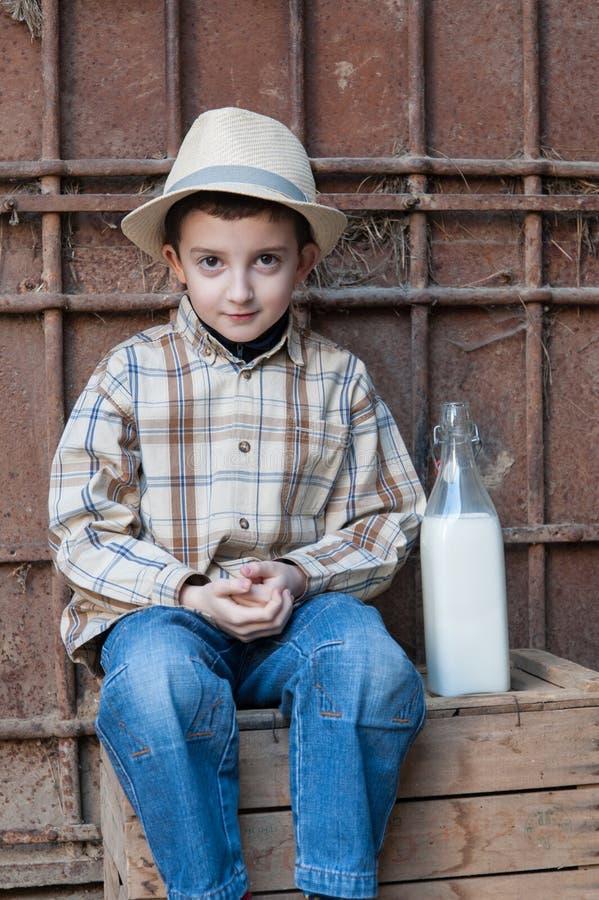 Barnsammanträde på en ask med en flaska av komjölk royaltyfria foton
