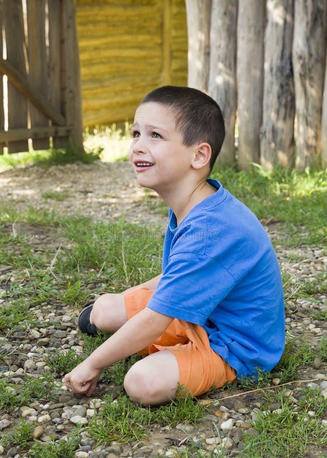 Barnsammanträde på jordning i trädgård royaltyfria bilder