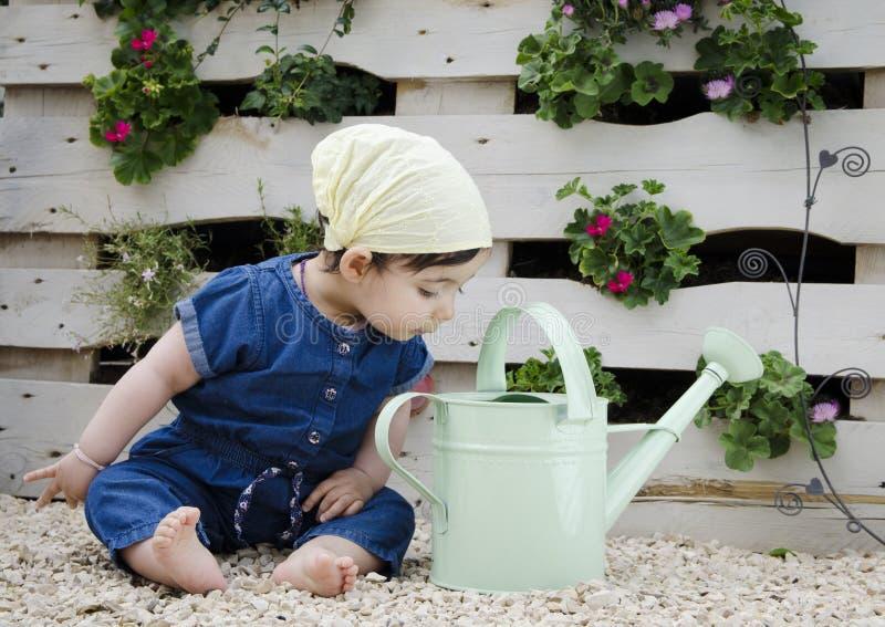 Barnsammanträde på jordningen, i att arbeta i trädgården dräkten med blomman i bakgrunden arkivbilder