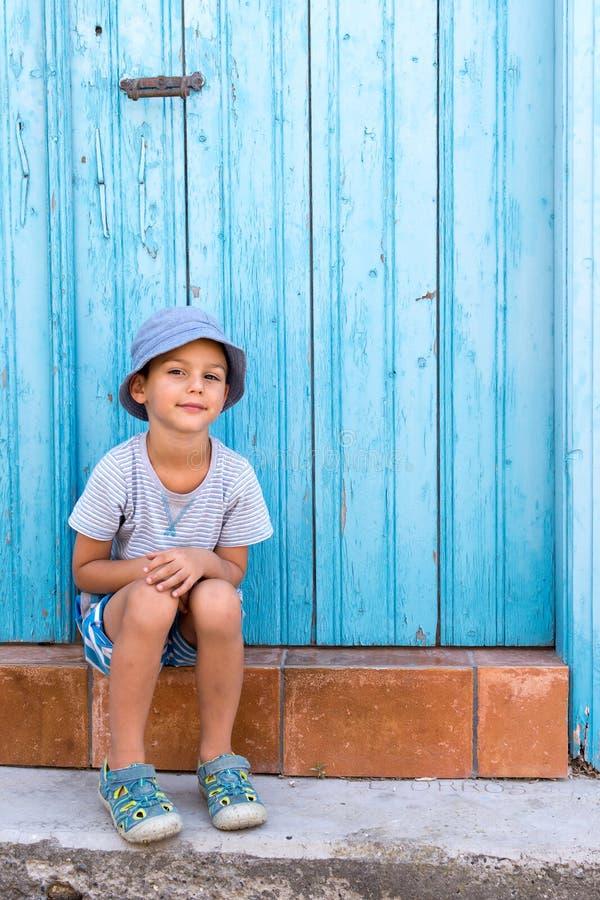 Barnsammanträde på ytterdörren fotografering för bildbyråer