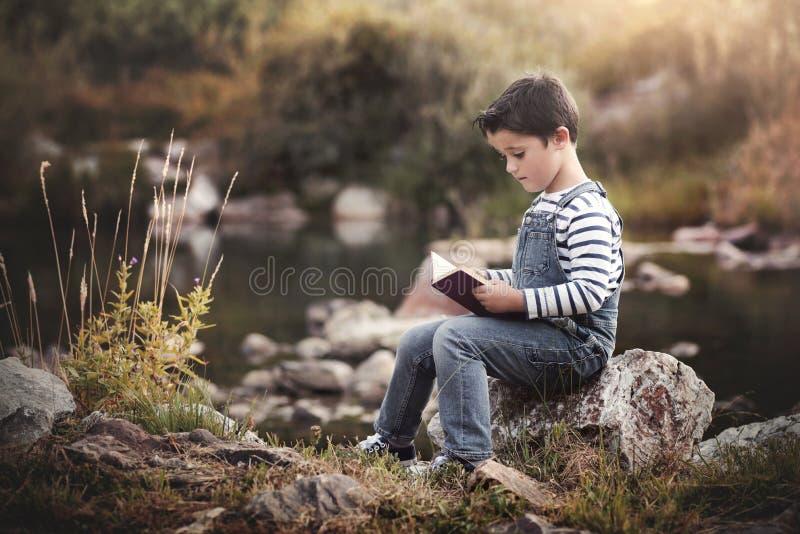 Barnsammanträde som läser en bok arkivfoto