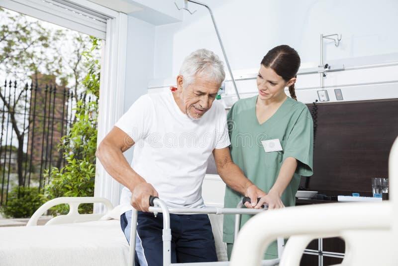 Barnsjuksköterska Helping Patient In som använder Walker At Nursing Home arkivfoto