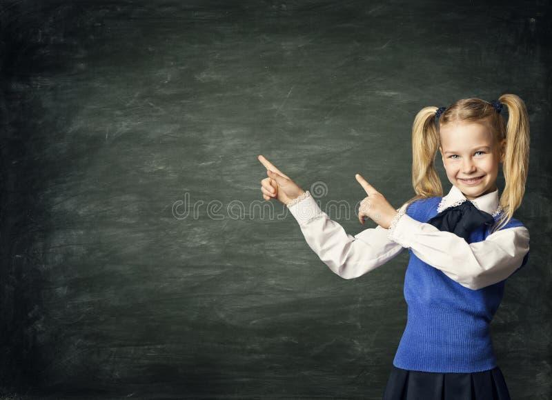 Barnskolaflicka som pekar svart tavla, ungestudent Black Board royaltyfria foton