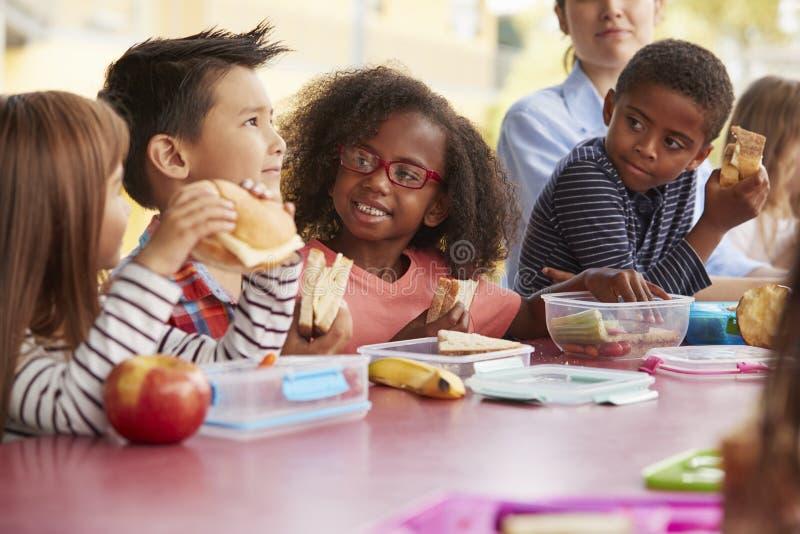 Barnskolaungar som äter lunch som tillsammans talar på en tabell arkivfoto