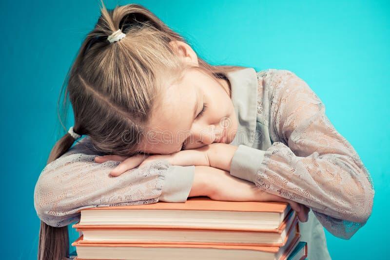Barnskolflickan läste skolflickan avverkar sömn på en bunt av böcker ing en bok på blå bakgrund royaltyfri foto