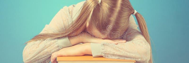BarnskolflickareadSchoolgirl avverkar sömn på en bunt av böcker ing en bok på blå bakgrund royaltyfri foto