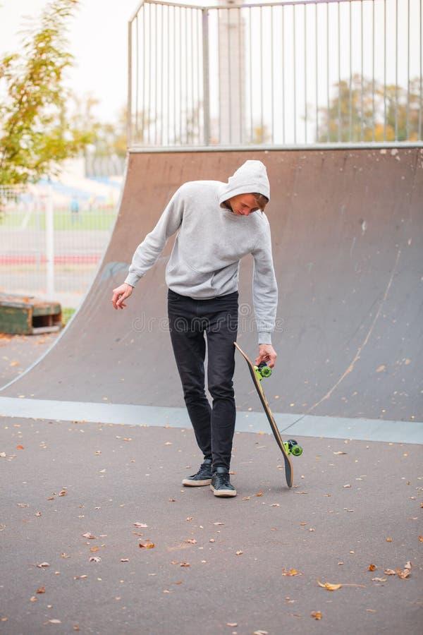 Barnskridskopojken som gör trick, i att åka skridskor, parkerar utomhus begrepp isolerad sportwhite fotografering för bildbyråer