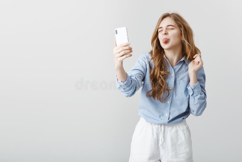 Barnslig flickvän som talar med vännen via internet Bekymmerslös attraktiv europeisk kvinna, hållande smartphone som tar royaltyfria foton