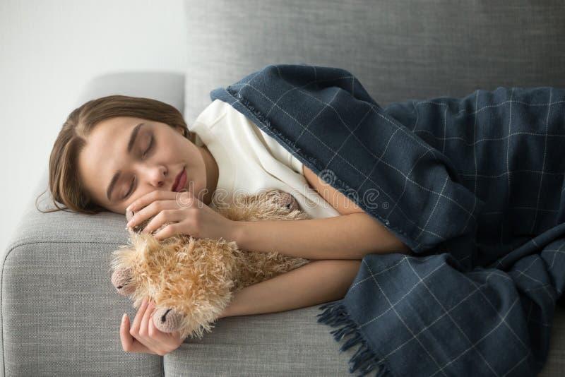 Barnslig kvinna som sover på den mjuka bekväma soffan med välfyllt till fotografering för bildbyråer