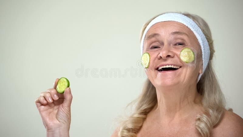 Barnslig positiv dam som applicerar gurkaframsidamaskeringen, optimistisk inställning för att åldras royaltyfri bild