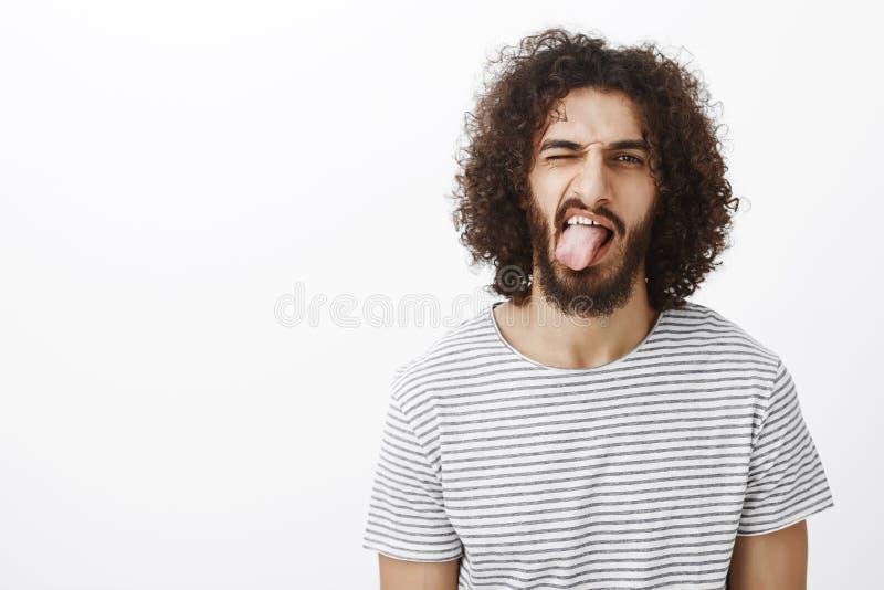 Barnslig snygg östlig grabb med skägget och lockigt hår som visar tungan och playfully blinkar och att känna sig bekymmerslöst oc fotografering för bildbyråer