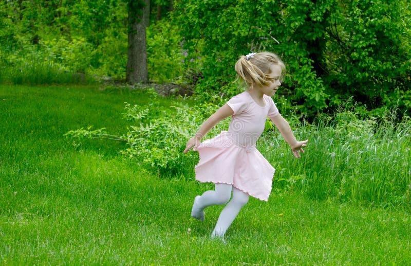 Barnspring till och med en trädgård royaltyfri bild
