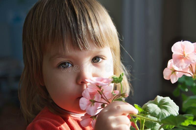 Barnstående med vårblommor, känslig lycka för unge, glat folk utan vårallergi arkivfoto
