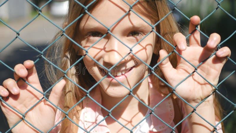 Barnstående som ler vid det metalliska staketet för skola, lyckligt skratta för liten flickaframsida royaltyfri bild