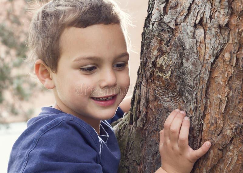 Barnstående vid trädet arkivbilder