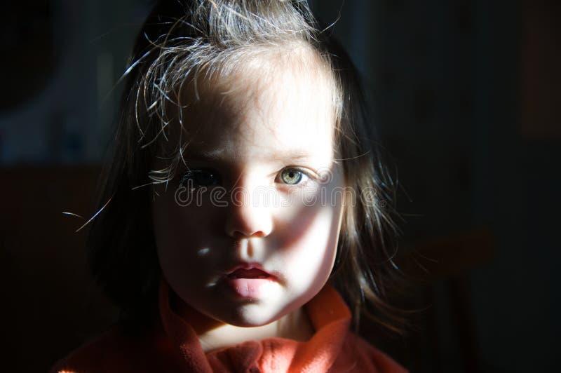 Barnståendehalvan tände gullig litet barnframsida med gråa ögon arkivfoton