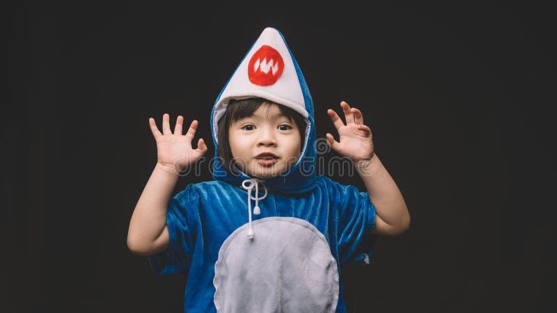 Barnståenden med behandla som ett barn hajdräkten i studio arkivfoto