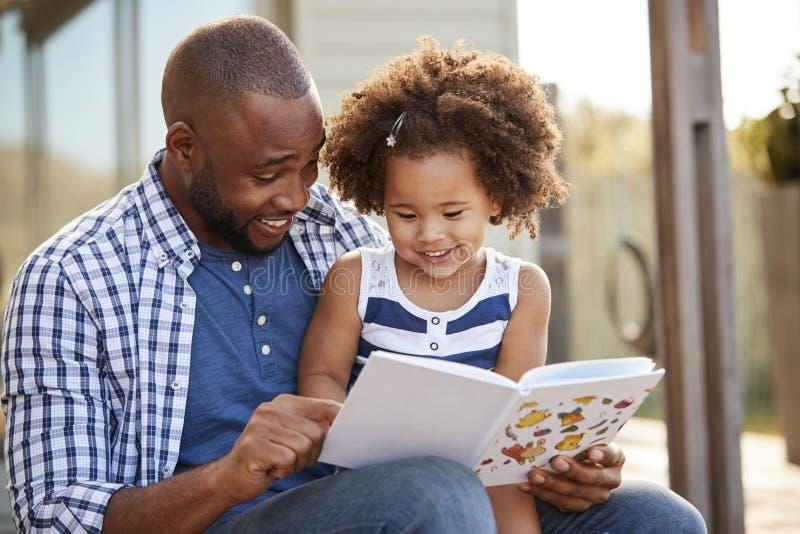 Barnsvartfader och dotterläsebok utanför arkivfoton