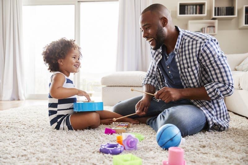 Barnsvartfader som spelar med dottern i vardagsrummet fotografering för bildbyråer