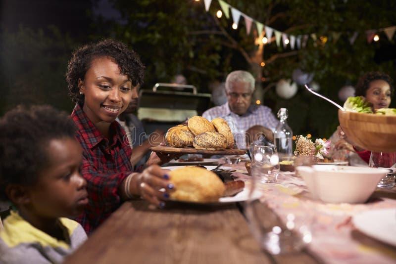 Barnsvartmoder som tjänar som henne sonmat på en familjgrillfest royaltyfria foton
