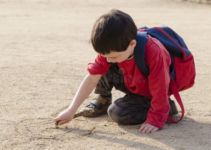 Barnteckning in i sand fotografering för bildbyråer