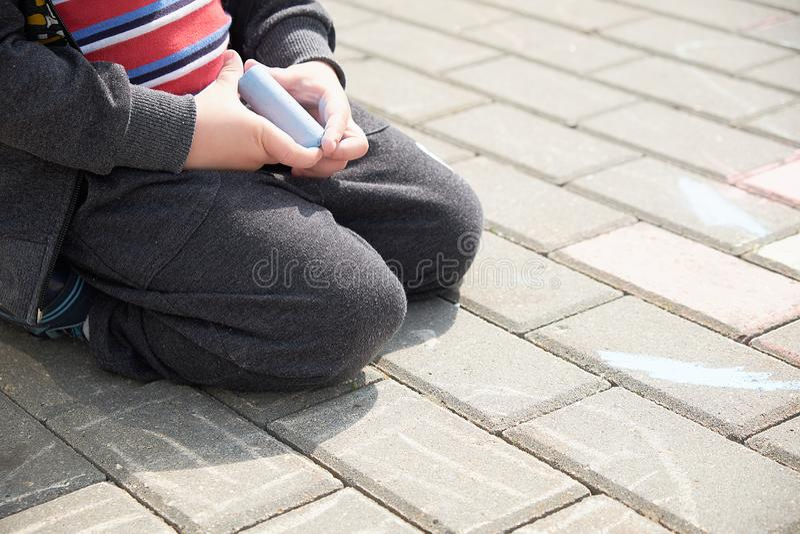 Barnteckning med krita på asfalt pojke som bara spelar i gatan rymma ett stycke av krita i hans fingrar arkivbilder