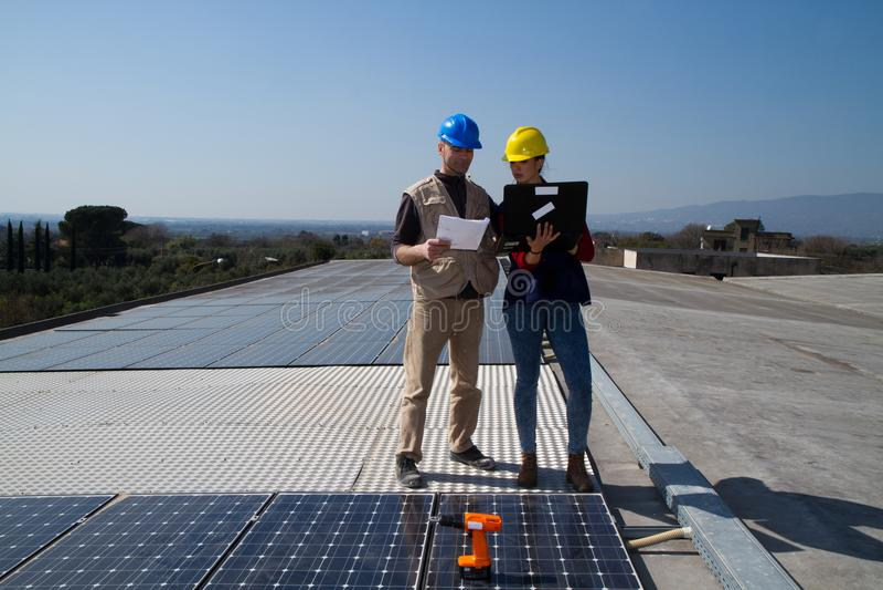 Barnteknikerflicka och kompetent arbetare på ett tak arkivfoton