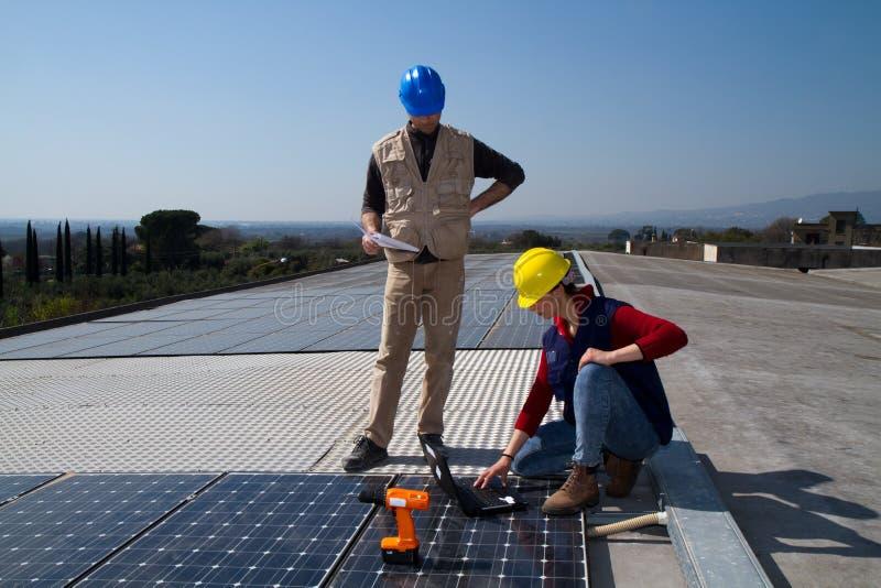 Barnteknikerflicka och kompetent arbetare på ett tak royaltyfria foton