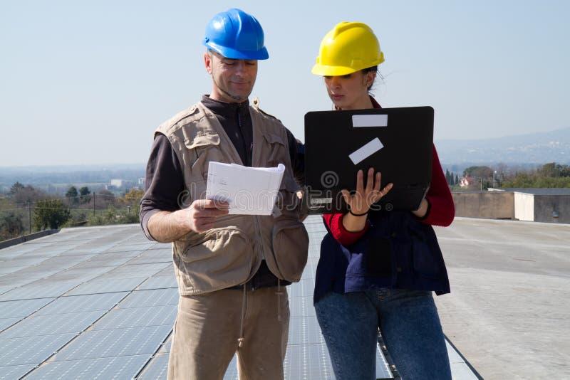 Barnteknikerflicka och kompetent arbetare på ett tak arkivbild