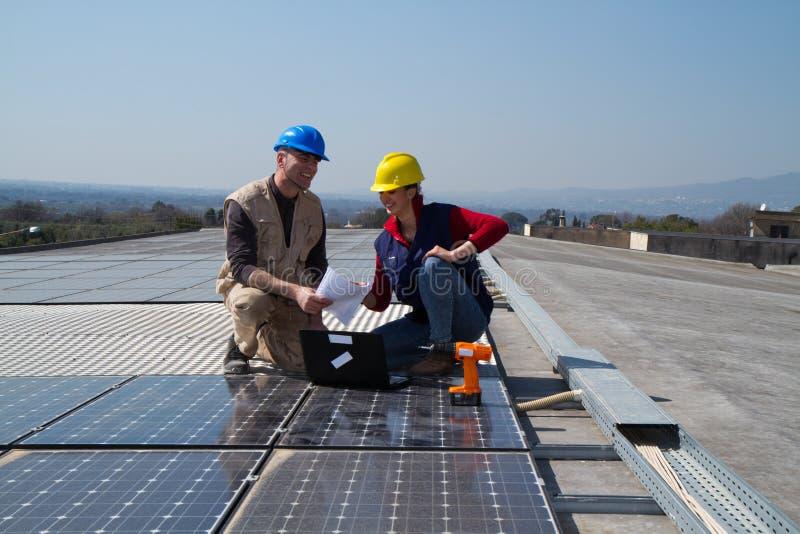 Barnteknikerflicka och kompetent arbetare på ett tak royaltyfri bild