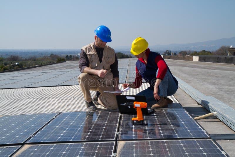 Barnteknikerflicka och kompetent arbetare på ett tak fotografering för bildbyråer