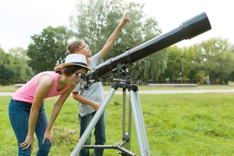 Barntonåringar i parkera som ser till och med ett teleskop fotografering för bildbyråer