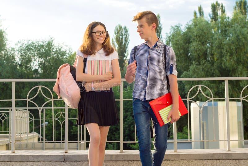Barntonåringar med ryggsäckar, läroböcker, anteckningsböcker går till skolan, tillbaka till skolan arkivbild