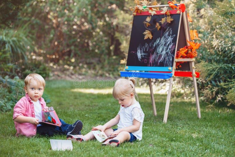 Barnunge-, pojke- och flickasammanträde i gräs utanför, genom att dra staffli med böcker som läser studera att lära arkivbilder