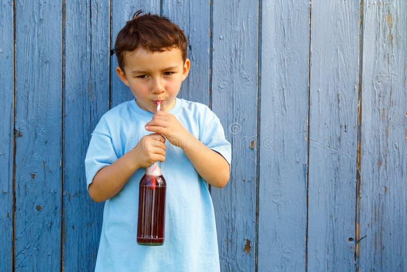 Barnungepys som dricker ou för det fria för lemonaddrink utomhus- royaltyfri fotografi
