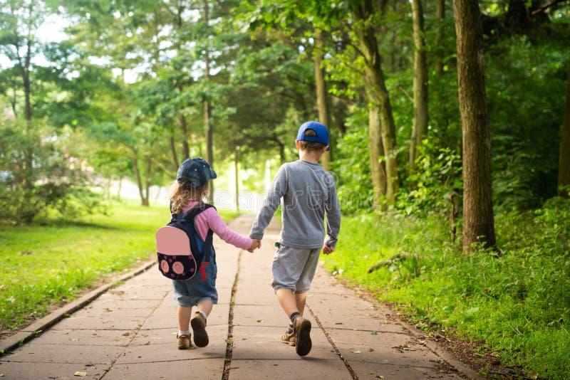 Barnvänner som går i sommar, parkerar och rymmer händer arkivfoton