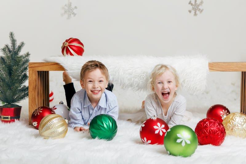 Barnvänner som tillsammans lägger under träbänken som skrattar och att fira jul eller nytt år royaltyfria foton