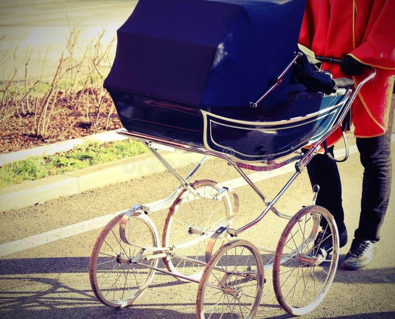 barnvagn som skjuts av en person arkivfoto