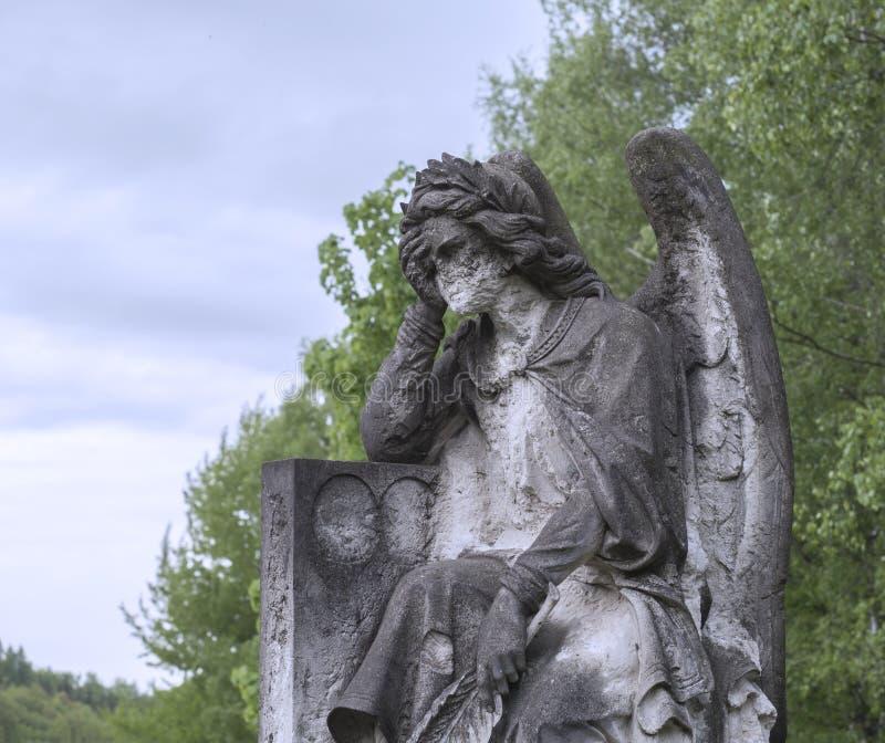 Barock staty för gammal sten av det ledsna greving hållande huvudet för ängel i mummel royaltyfri fotografi